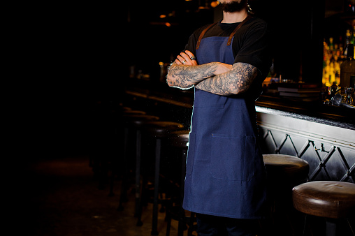 1003493404 istock photo Barman with tattoo on hands dressed in blue apron 989297628