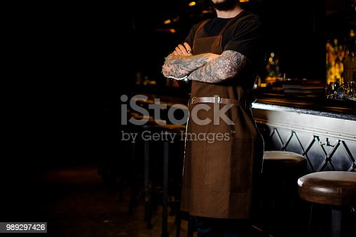 1003493404istockphoto Barman with tattoo on hands dressed in brown apron 989297426