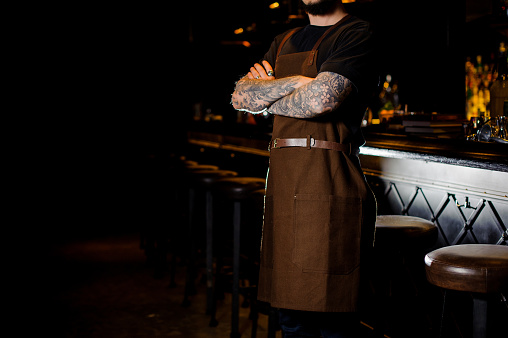 1003493404 istock photo Barman with tattoo on hands dressed in brown apron 989297426