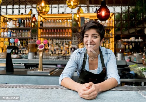 Happy female bartender working at the bar and looking at the camera smiling