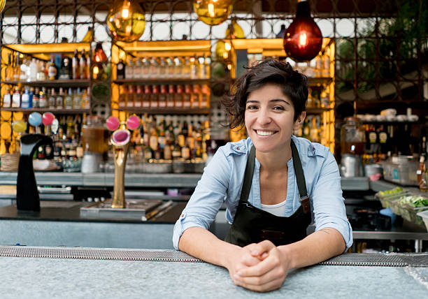 Barman working at a bar Happy female bartender working at the bar and looking at the camera smiling bartender stock pictures, royalty-free photos & images