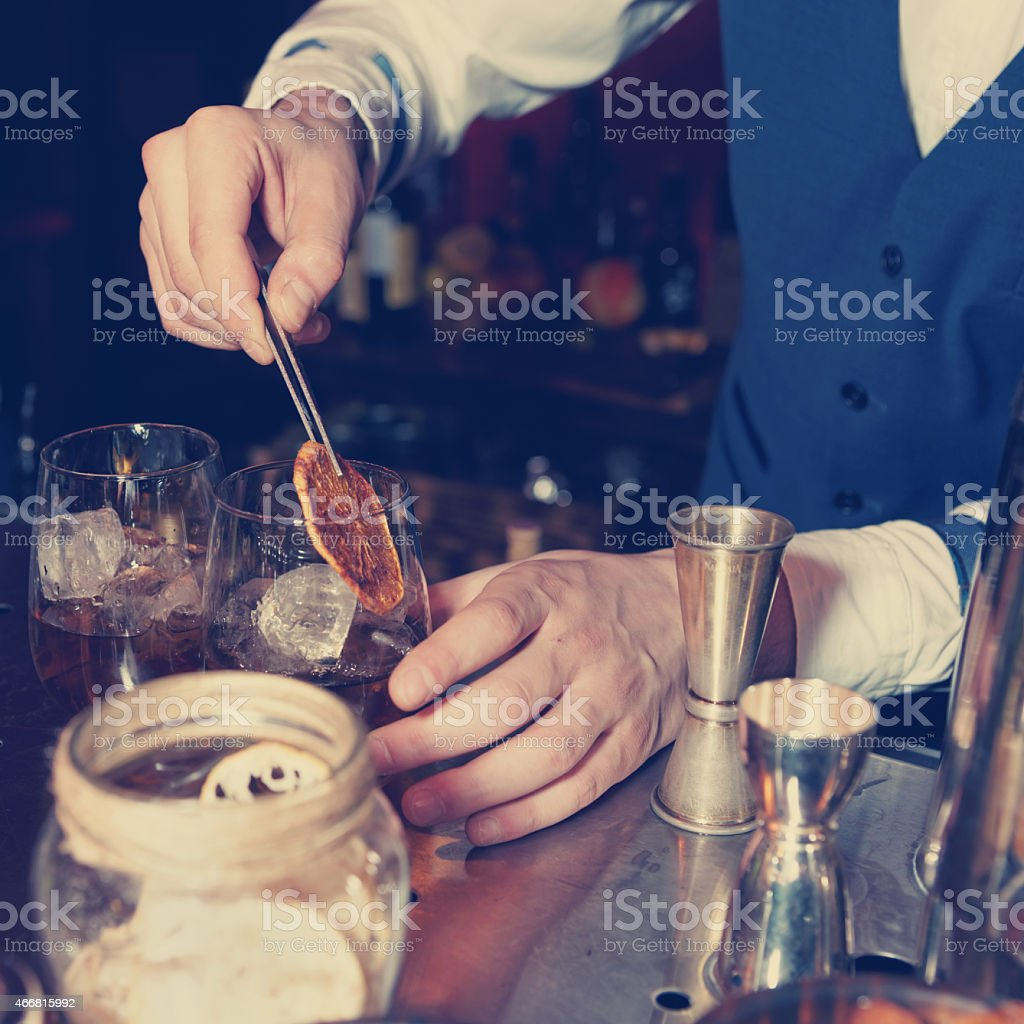 Barman works at bar counter, toned stock photo