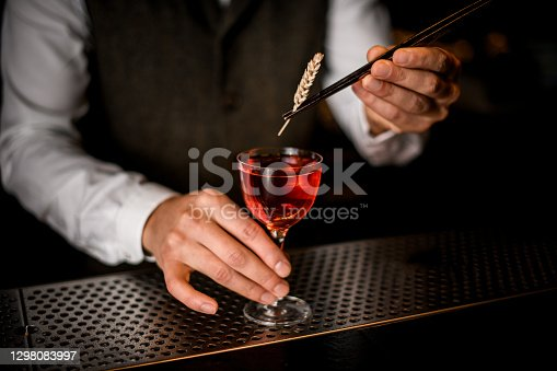 barman's hand holds glass of red alcoholic drink and decorates it with wheat spikelet using tweezers