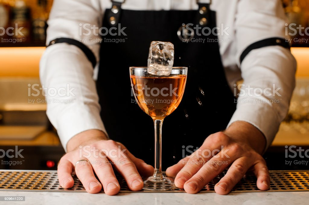 Barmans hands holding a glass with alcoholic drink and ice cube stock photo