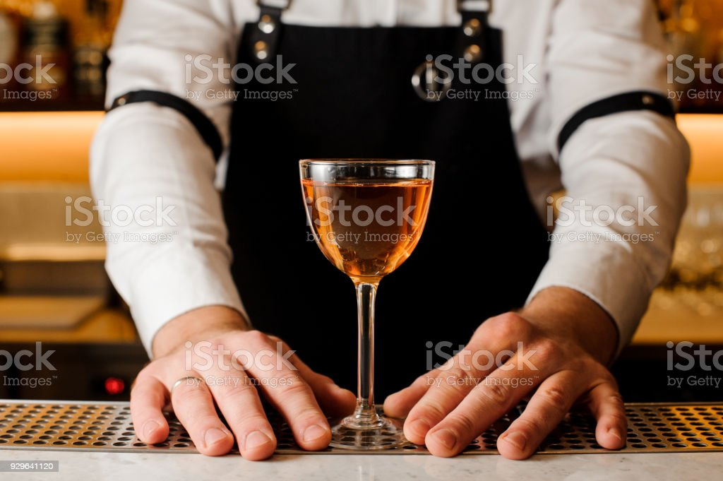 Barmans hands holding a glass with alcoholic drink stock photo