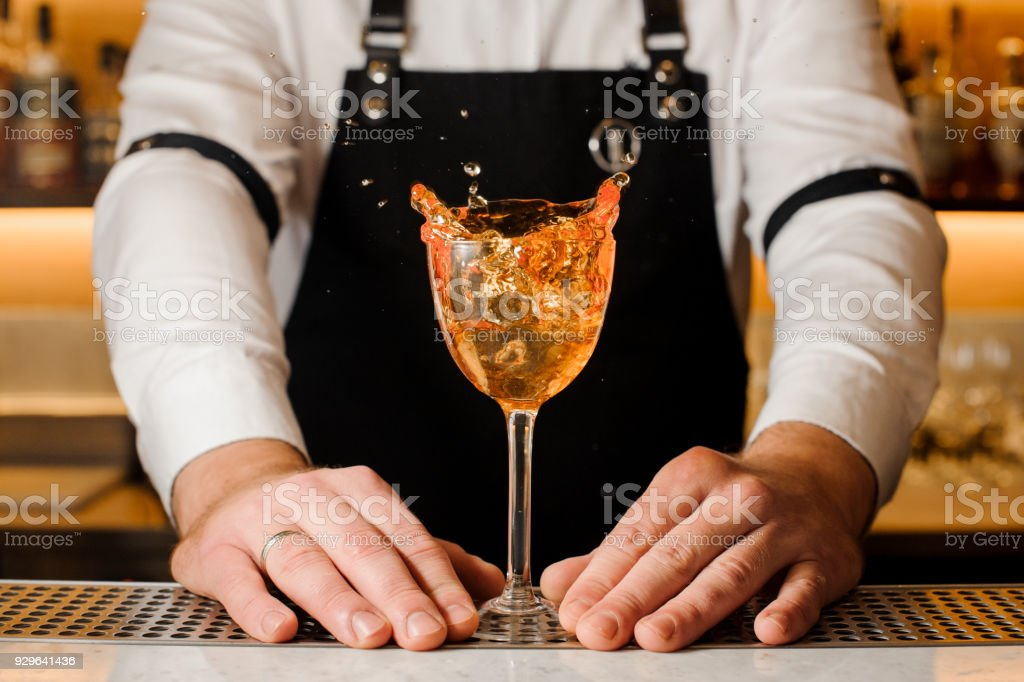 Barmans hands holding a glass with splashing alcoholic drink stock photo