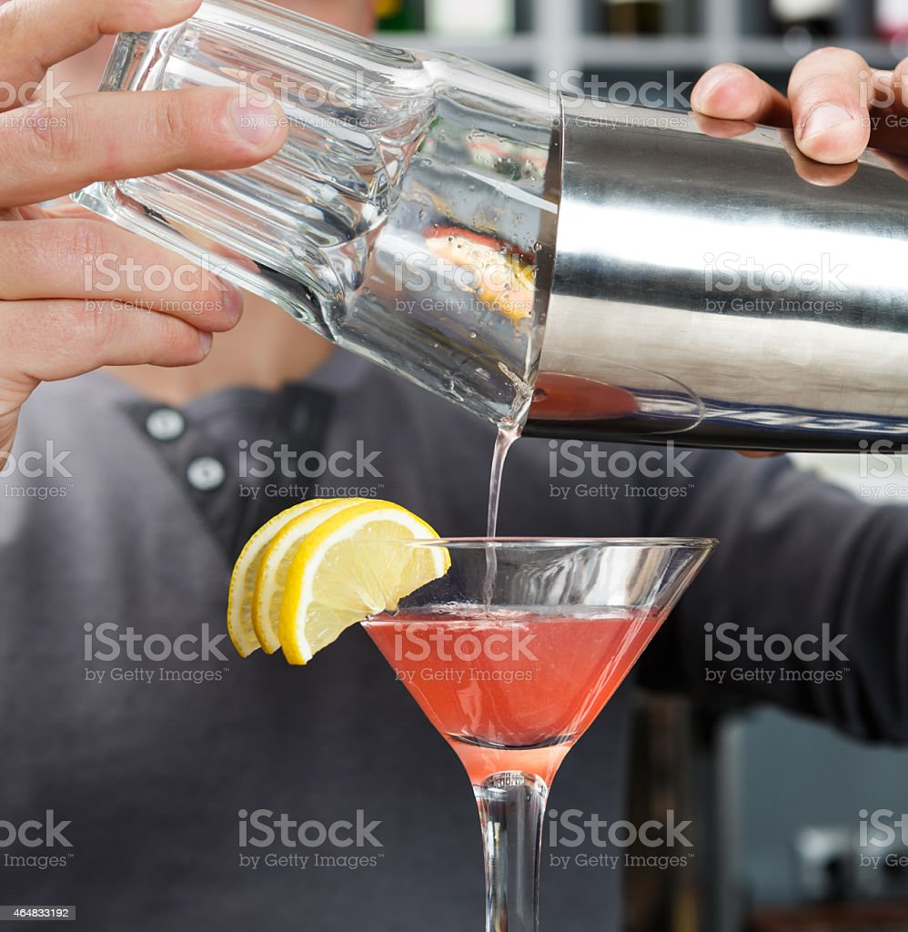 Barman's hands mixing cosmopolitan cocktail stock photo