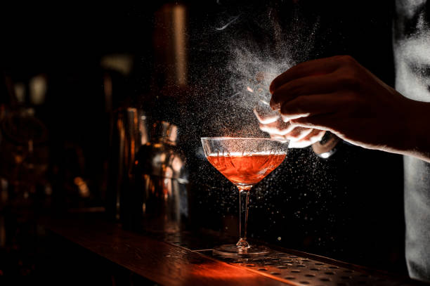 Barmans hands sprinkling the juice into the cocktail glass Barmans hands sprinkling the juice into the cocktail glass filled with alcoholic drink on the dark background bartender stock pictures, royalty-free photos & images