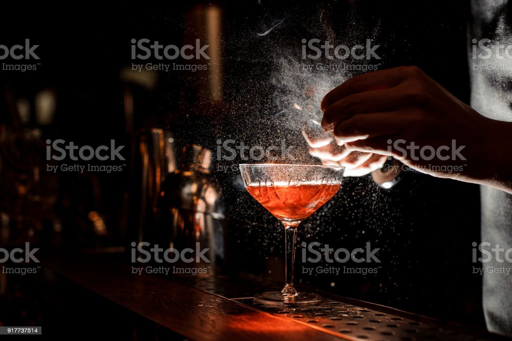 Barmans hands sprinkling the juice into the cocktail glass stock photo