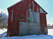 This is an old red barn in the shade. It is surrounded by snow. There is blue sky in the background.