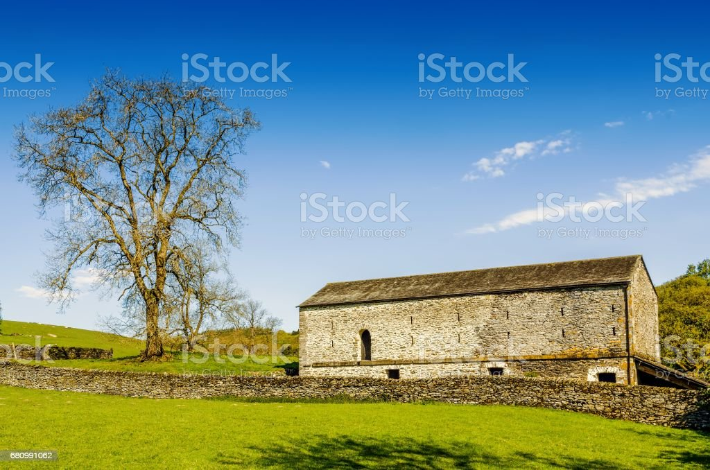 A barn and tree set in English countryside with a green field in the foreground under a blue sky royalty-free stock photo