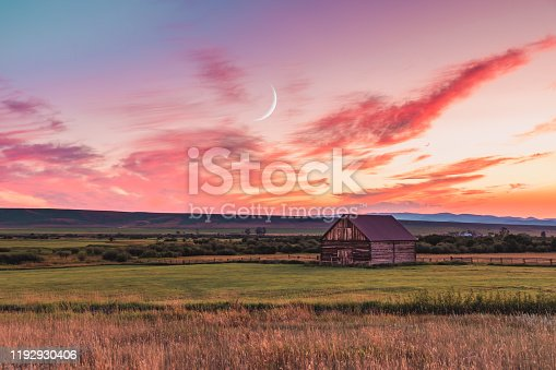 A beautiful sunset in a rural Montana scene. A simple barn sits in a field as the sun sets while the crescent moon rises above.