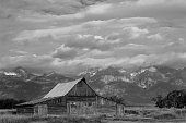 Barn with adj black and white with cloudy skies