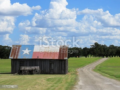 barn & buckboard wagon by rural road in Texas