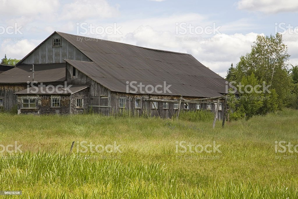 Barn Dwelling Behind a Field royalty-free stock photo