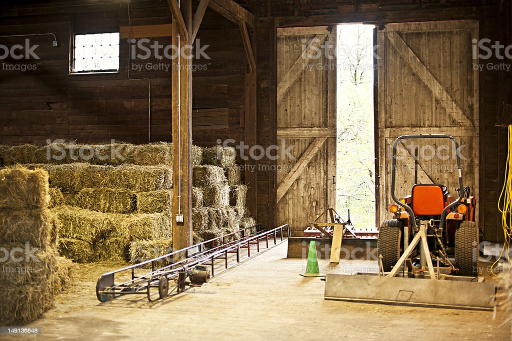 Barn interior with hay bales and farm equipment stock photo