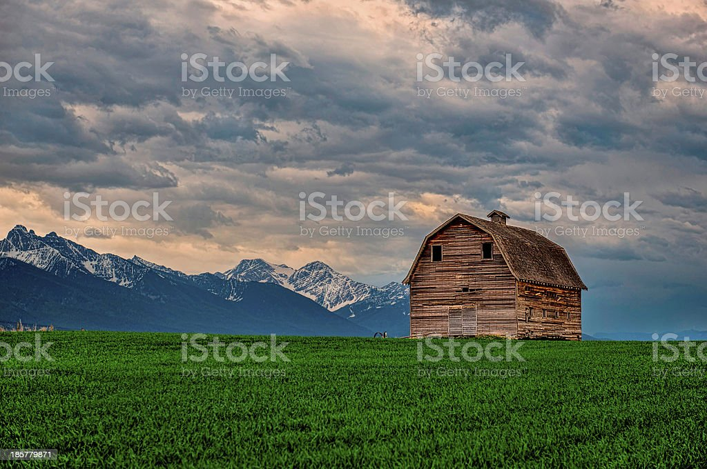 Barn Large barn in Flathead Valley, northwestern Montana with storm. Agricultural Field Stock Photo
