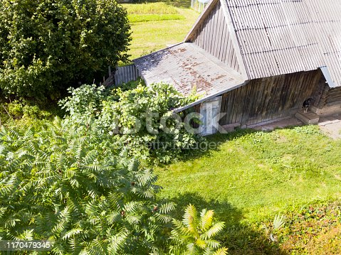Bird eyes view of a barn with tethered dog in the foreground