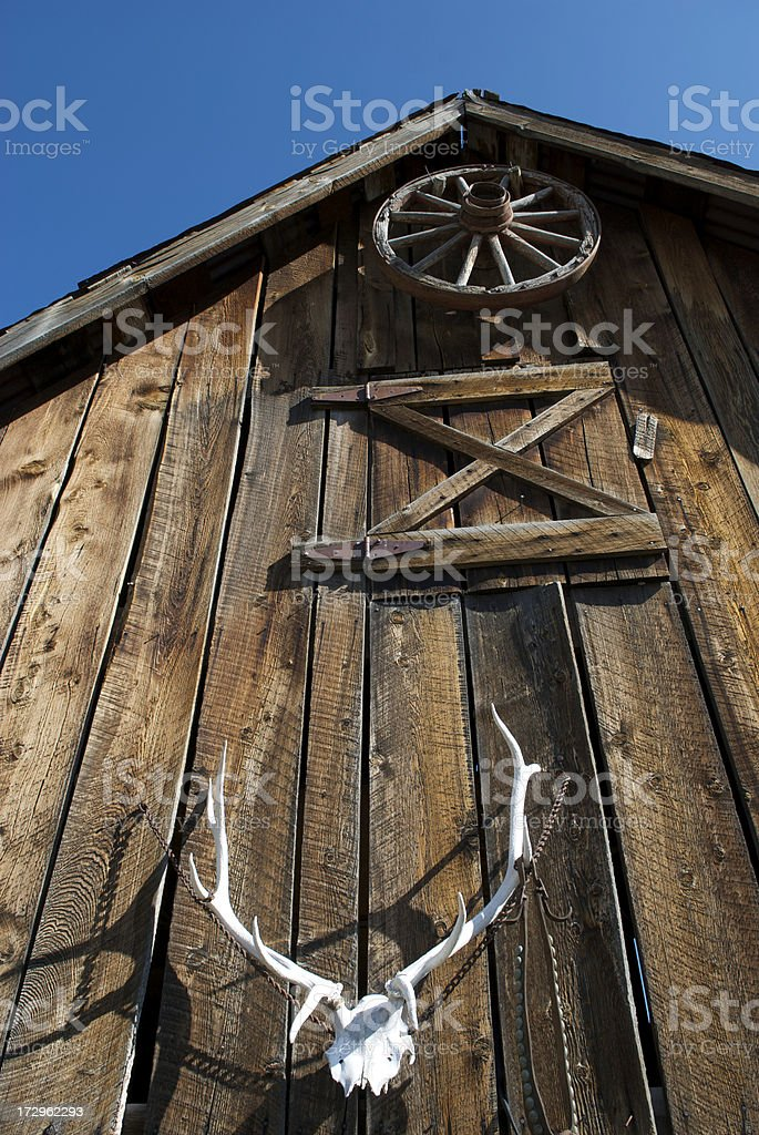 Barn with Wheel and Antlers stock photo