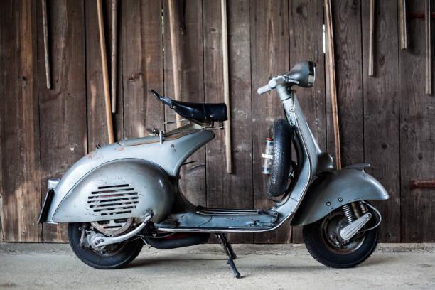 Barnfind alte, rostige, gebrauchte italienische Motorrad Roller auf Holzwand – Foto