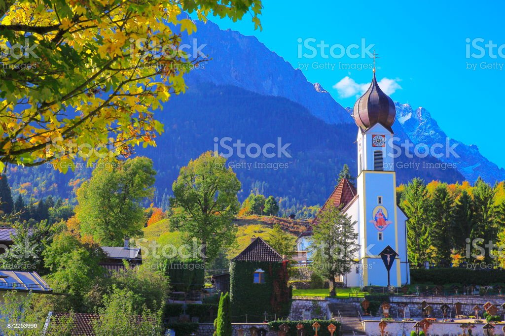 Baroque church in Grainau Alpine village with Zugspitze, Waxenstein and Alpspitze view – dramatic landscape in Bavarian alps, Germany - Majestic alpine landscape in gold colored autumn, dramatic Snowcapped mountains – Garmisch, Bavaria, Germany stock photo