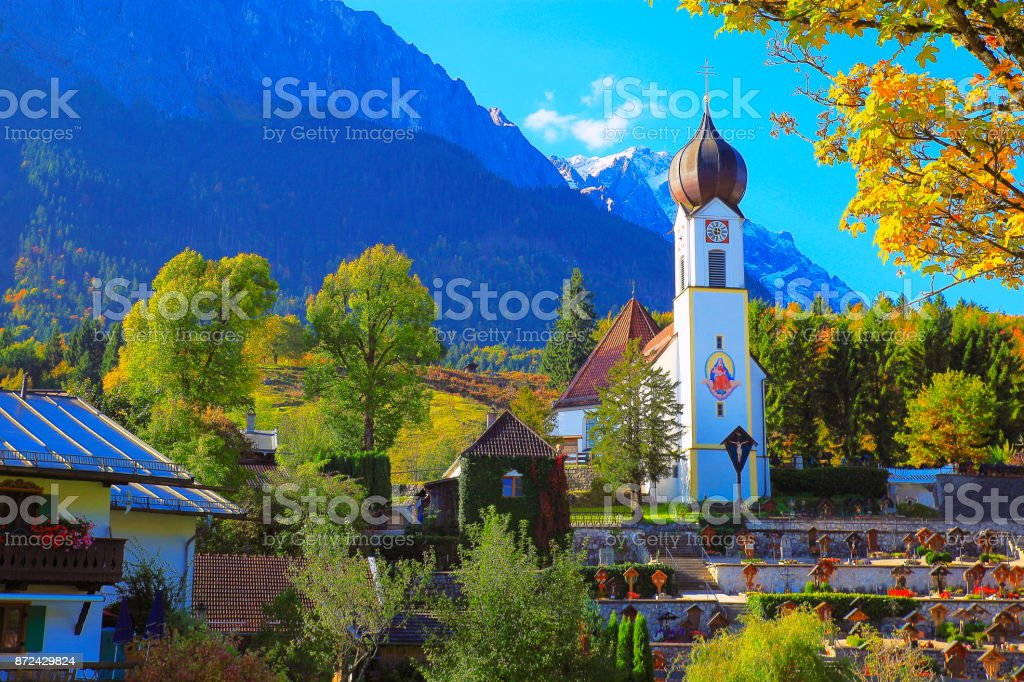 Baroque church in Grainau Alpine village with Zugspitze, Waxenstein and Alpspitze view– dramatic landscape in Bavarian alps, Germany - Majestic alpine landscape in autumn – Garmisch, Bavaria, Germany stock photo