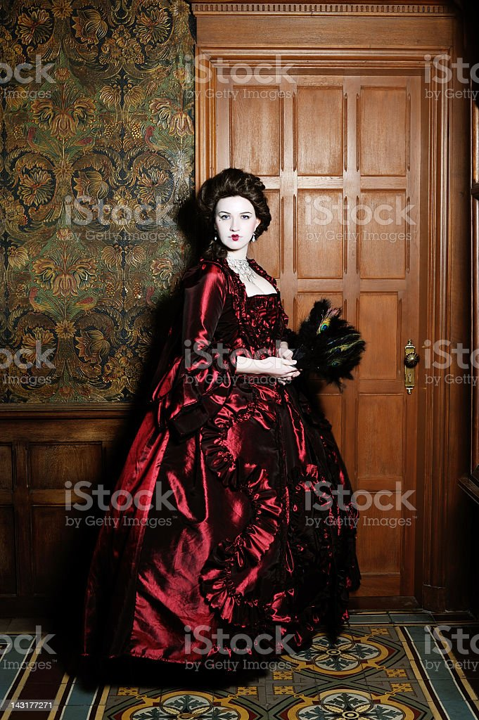 Baroque Lady in Red Dress before Wood Door Leather Wall royalty-free stock photo