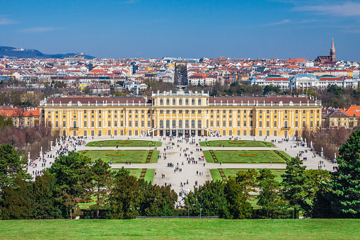 Austria - Vienna - The beautiful baroque palace Schonbrunn and its gardens and lawns with panorama of Vienna city on background