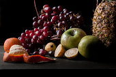 Renaissance photography or chiaroscuro style of still life fruits photography with grapes, pineapple, green apples, guavas, tangerines, and red grapes. oil painting style