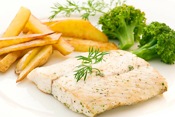 Barramundi Filet with Chips Barramundi filet with chips as closeup on a white plate perch fish stock pictures, royalty-free photos & images
