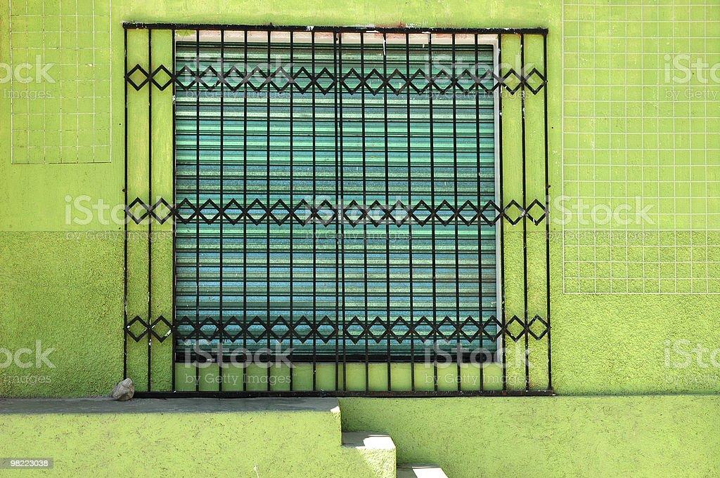 Barred Window on Green Wall stock photo