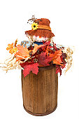 A Scarecrow in a barrel of leaves.
