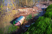 Barrel of toxic waste dumped into the river along with plastic bottles and other garbage polluting ecosystem.