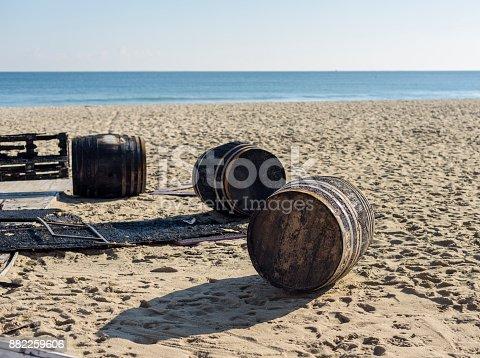 three burned wooden barrel on a beach