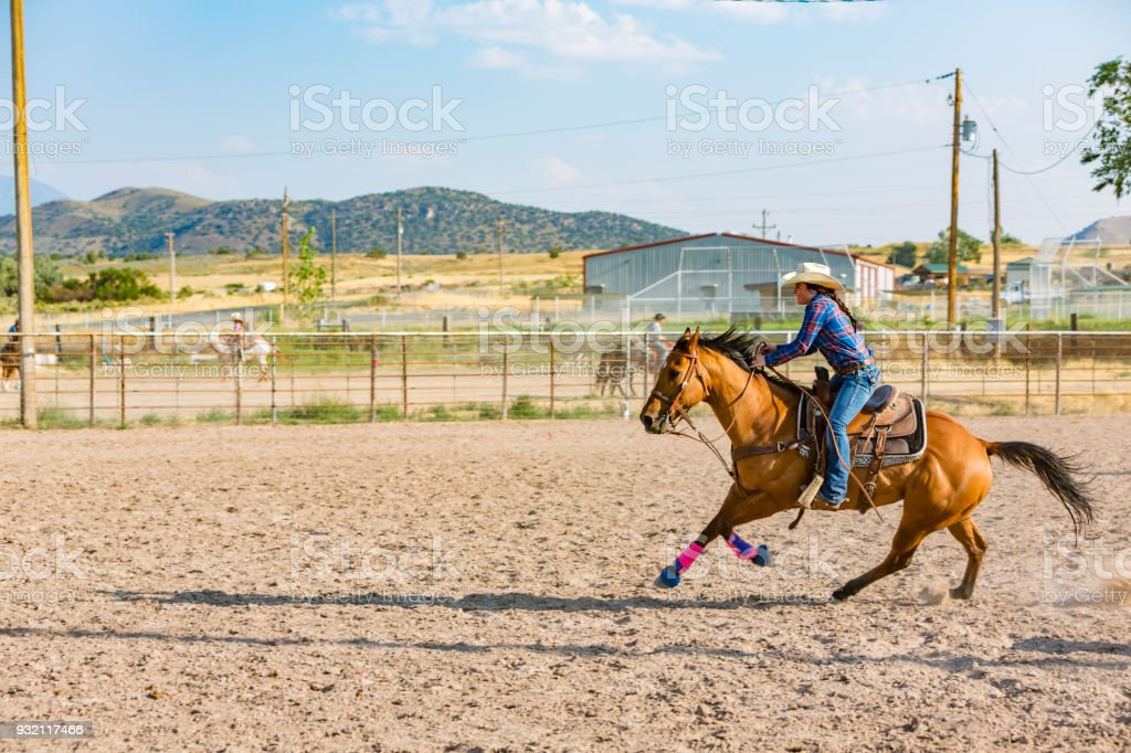 Barrel Racing Cowgirls at a Dusty Rodeo stock photo