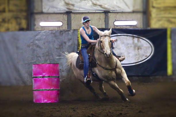 Barrel Racing Barrel racing indoors on palomino horse around pink barrel palomino stock pictures, royalty-free photos & images