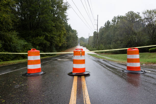 Barricades and police tape block a flooded road stock photo