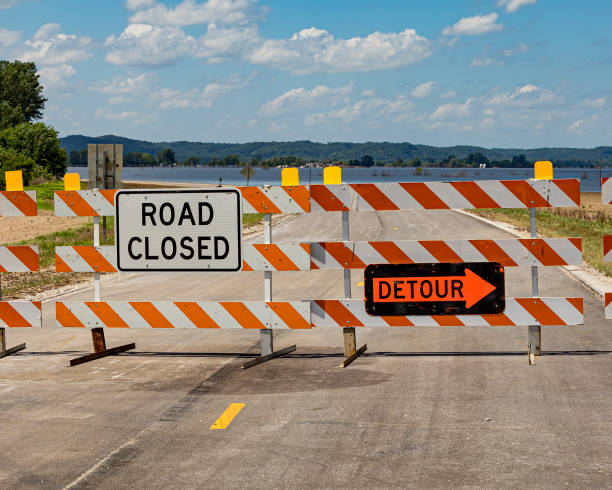Barricades and signs warn of a road closed due to flooding along the Mississippi River stock photo