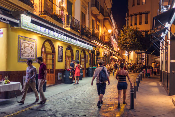 Barrio Santa Cruz, Sevilla People out in the evening in the popular historical Santa Cruz neighborhood in Seville, Spain. santa cruz seville stock pictures, royalty-free photos & images