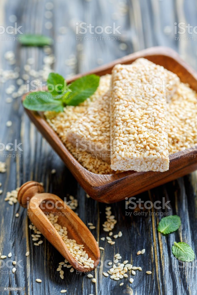 Bars with sesame in honey glaze and a scoop with sesame seeds. stock photo