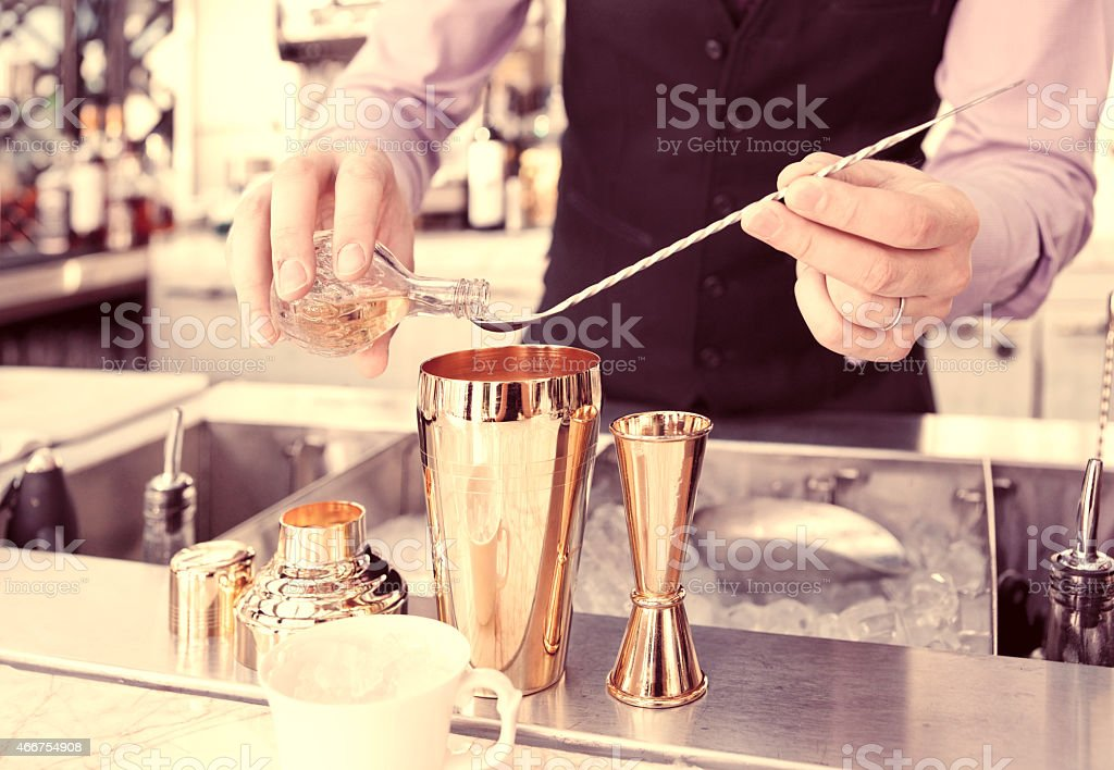 Bartender adding a liquid substance into a cocktail shaker stock photo
