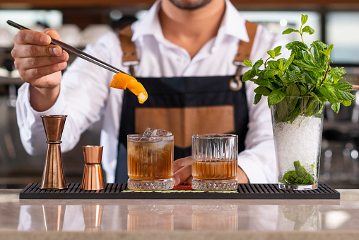 Male bartender adding lemon peel in a drink with tongs