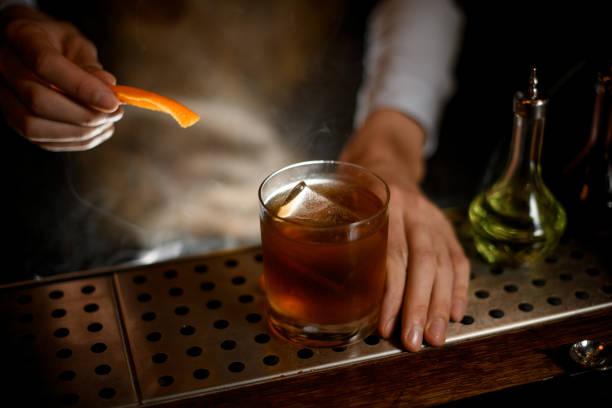 Bartender adding orange zest in whiskey glass stock photo