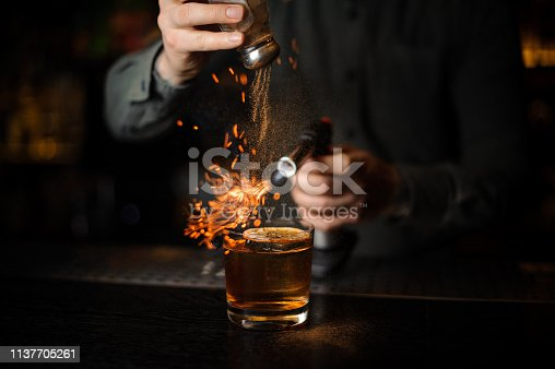 Bartender adding to a cocktail with ice cube and dry orange on it a cinnamon and flaming it with a burner on the bar counter in the dark.