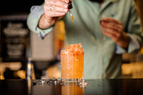 bartender adds bitter to summer cocktail - dark beer stock photos and pictures