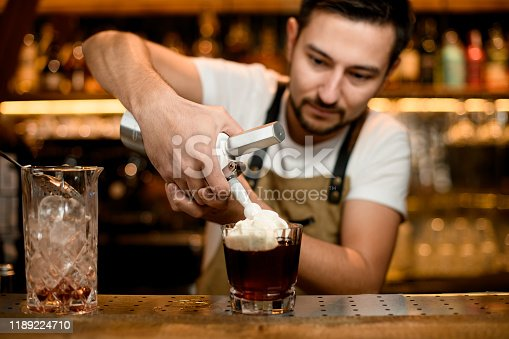 Stylish bartender adds whipped cream to alcohol cocktail in glass on wooden counter