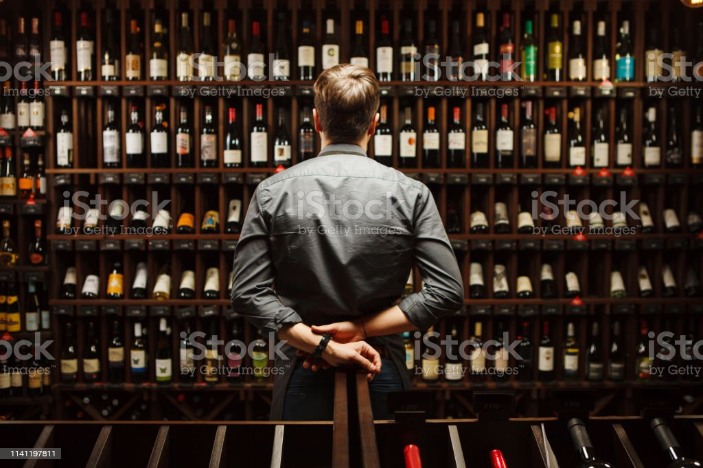 Bartender at wine cellar full of bottles with exquisite drinks Bartender at wine cellar full of bottles with exquisite alcohol drinks that have various sweet and sour tastes and dates of manufacture on large wooden shelves. Adult Stock Photo
