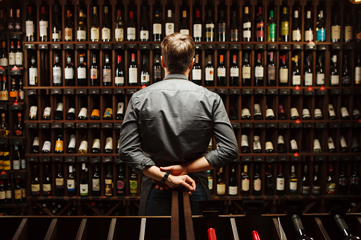 Bartender At Wine Cellar Full Of Bottles With Exquisite Drinks Stock Photo - Download Image Now