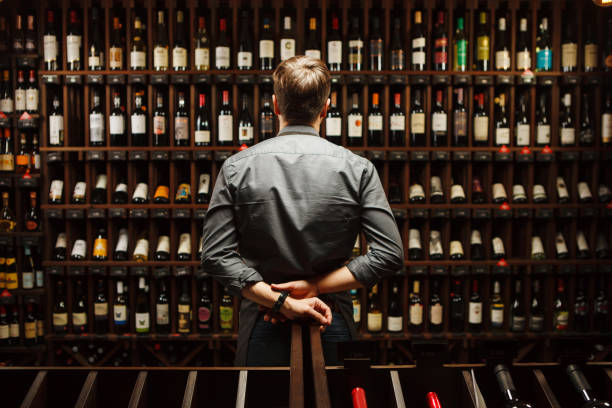 Bartender at wine cellar full of bottles with exquisite drinks Bartender at wine cellar full of bottles with exquisite alcohol drinks that have various sweet and sour tastes and dates of manufacture on large wooden shelves. wine cellar stock pictures, royalty-free photos & images
