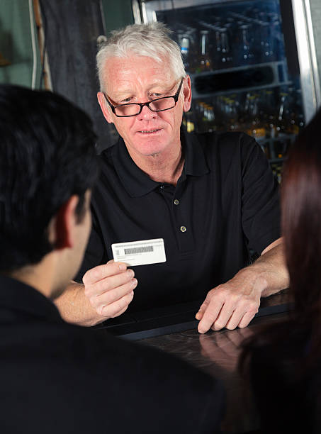 bartender checking id - identity card stock photos and pictures